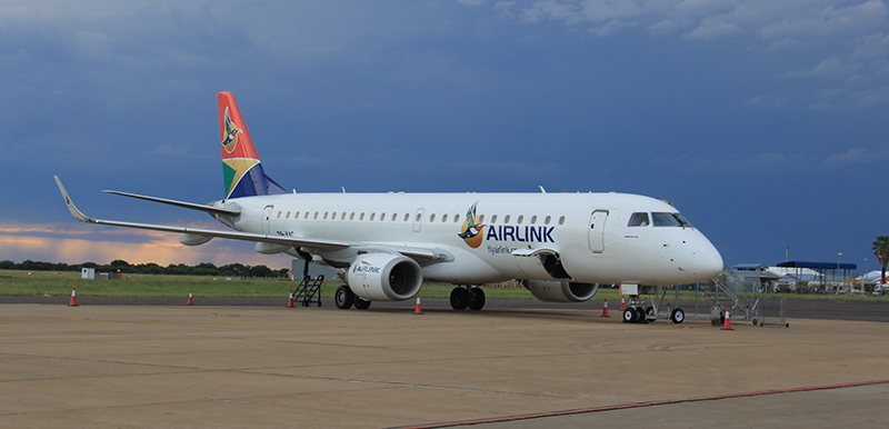 Airlink's Embraer E-190 on the tarmac at Kimberley Airport with thunderous skies.