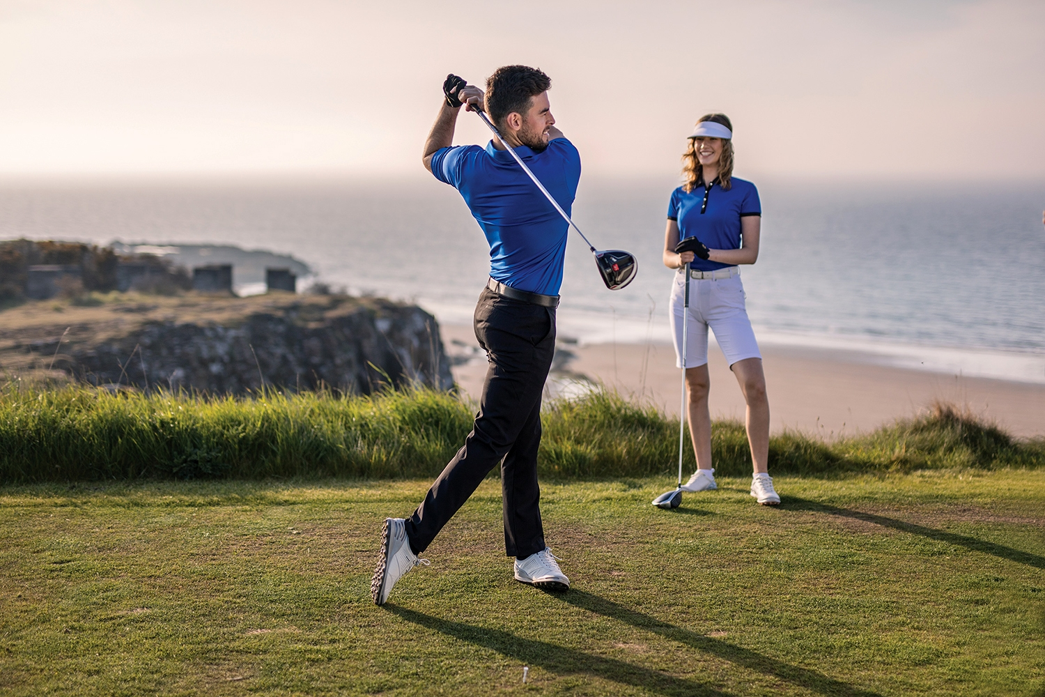 Couple wearing Sunderland Glenmuir golf outfits while playing golf