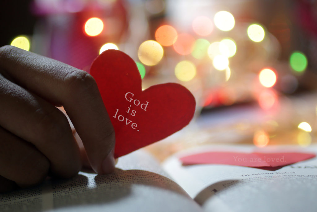 God is love. With red heart shape in hand.