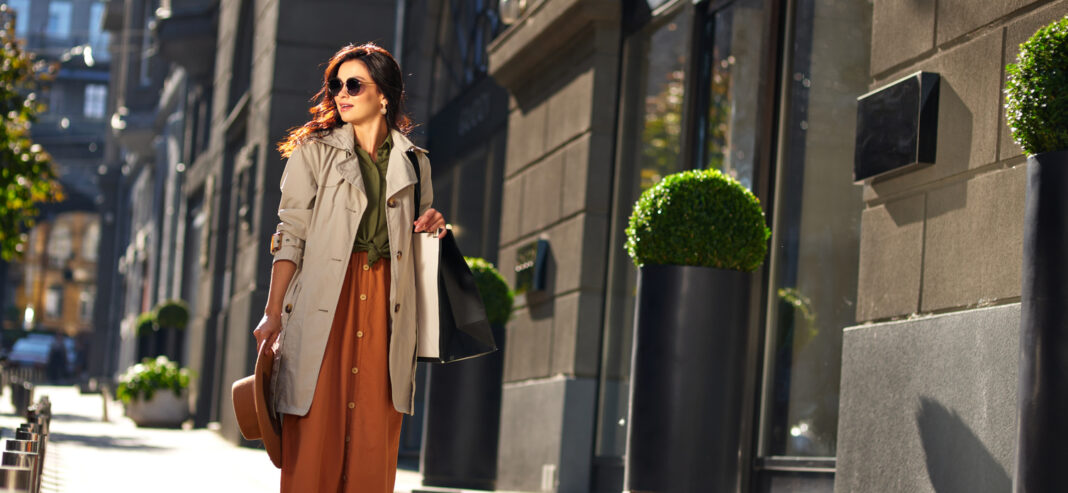 Young stylish woman with shopping bag walking city streets on a warm autumn day, visiting fashion boutiques and shops